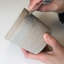 3: Mishima, or inlay. I have scratched a series of lines into the bare clay of this beaker. Then I have filled/covered the design with grey slip. Here I am using a flexible metal kidney to scrape away the excess colour. Once fired this pot will have a white body and the design will be grey.