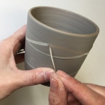 4: Paper resist. I cut some thin strips of newspaper and soaked them in water before applying them to the beaker. Then I covered the inside and outside with grey slip. Here I am pulling off the paper to reveal the bare clay beneath. As with the sgraffito pot, this one will fire grey with white decoration.